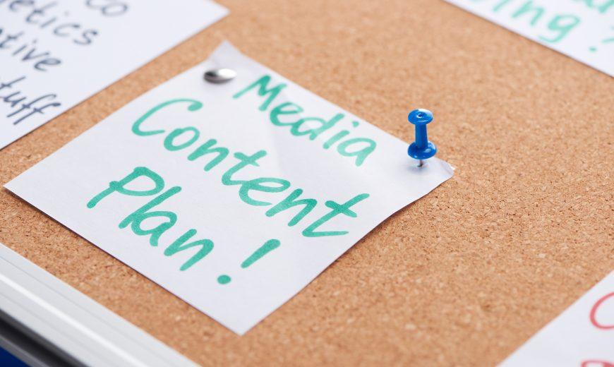 Tarjeta de papel con inscripción de plan de contenido de medios fijada en tablero de oficina de corcho